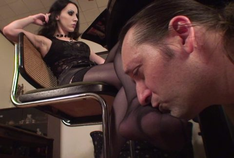 While Mistress Bojana is Reading a Magazine, Her Slave Under The Table Kisses Her Feet in Stockings